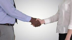 Mains de poignée de main d'homme d'affaires et de femme d'affaires sur le fond de gradient banque de vidéos