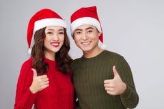 Mains de port de geste de chapeau de Noël de couples asiatiques Image stock