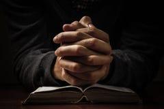Mains de prière avec la bible Image stock