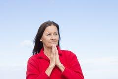 Mains de prière de femme réfléchie intéressée Photos libres de droits