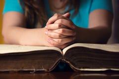 Mains de prière sur la bible photographie stock libre de droits