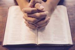 Mains de prière sur la bible Images libres de droits