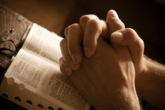Mains de prière sur une bible ouverte Image libre de droits