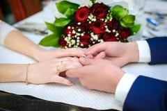 Mains de prise d'amants à la table Image stock