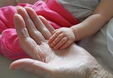 Mains de prise d'arrière grand-mère et d'arrière-petite-fille image stock
