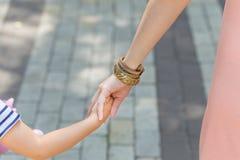 Mains de prise de mère et de fille pendant la promenade de ville Photos libres de droits