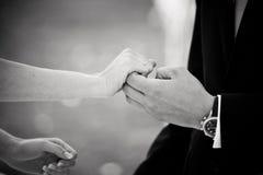 Mains de prise de marié et de jeune mariée à un mariage images stock