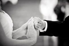 Mains de prise de marié et de jeune mariée à un mariage photo stock