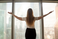 Mains de propagation de femme d'affaires sûre s'élevant à la grande fenêtre, Photo stock