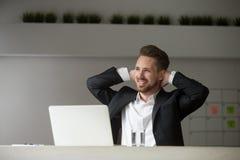 Mains de repos de sourire d'homme d'affaires rêveur derrière sa tête Photos stock