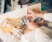 Mains de restaurateur fonctionnant avec le décor antique Photographie stock