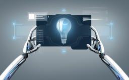 Mains de robot avec l'ampoule sur le PC de comprimé Photos libres de droits