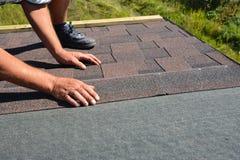 Mains de Roofer étendant Asphalt Shingles sur le toit de construction de maison Construction de toiture avec des bardeaux d'aspha images libres de droits