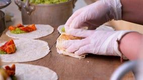 Mains de serveuse enveloppant le burrito complétant la tortilla vidéo 4K clips vidéos