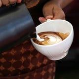 Mains de serveuse versant le lait faisant le cappuccino Photographie stock