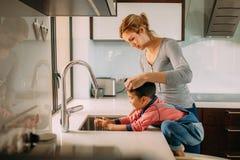 Mains de soin de lavage de mère et d'enfant dans un évier image stock