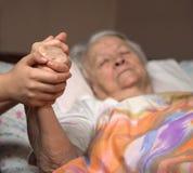 Mains de soin tenant les mains de vieille dame Photo stock