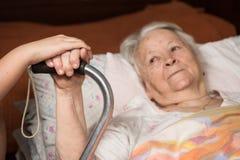 Mains de soin tenant les mains de vieille dame Photographie stock