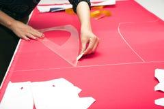 Mains de tailleur fonctionnant avec le tissu rose Photographie stock libre de droits