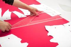 Mains de tailleur fonctionnant avec le tissu rose Image stock