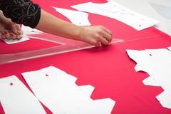 Mains de tailleur fonctionnant avec le tissu rose Photo stock