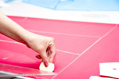 Mains de tailleur fonctionnant avec le tissu rose Image libre de droits