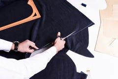 Mains de tailleurs coupant le tissu Images stock