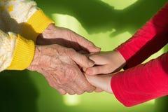 Mains de Th de grand-mère et de petit-enfant Images libres de droits