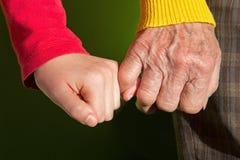 Mains de Th de grand-mère et de petit-enfant Image libre de droits