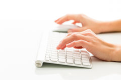 Mains de travailler de personne un clavier Photographie stock libre de droits