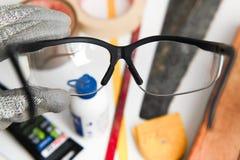 Mains de travailleur avec des verres protecteurs sur les outils dans le workb Photographie stock