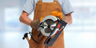 Mains de travailleur avec la scie électrique Image stock