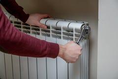 Mains de travailleur réparant le radiateur avec la clé Images libres de droits