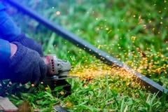 Mains de travailleur rectifiant ou coupant le métal avec la broyeur au chantier extérieur de pelouse ou de construction photos libres de droits
