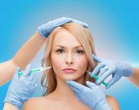 Mains de visage et d'esthéticien de femme avec des seringues Photographie stock libre de droits