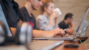 Mains des étudiants dactylographiant avec le clavier d'ordinateur portable dans le café 4K clips vidéos