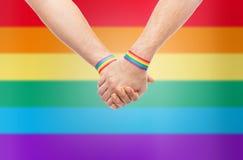 Mains des ajouter aux bracelets d'arc-en-ciel de fierté gaie Images stock