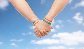 Mains des ajouter aux bracelets d'arc-en-ciel de fierté gaie Photo libre de droits