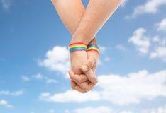 Mains des ajouter aux bracelets d'arc-en-ciel de fierté gaie Photos stock