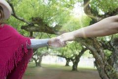 Mains des amants, des hommes et des femmes dans l'espace vert Images libres de droits