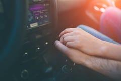 Mains des amants ensemble dans une fin de voiture  Photos stock