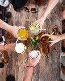 Mains des amis en cercle tenant des cocktails Images libres de droits