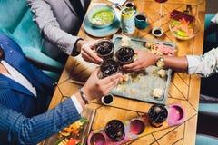 Mains des amis ensemble en cercle tenant les diff?rents cocktails avec de la glace sur le fond de la vieille table en bois photo stock