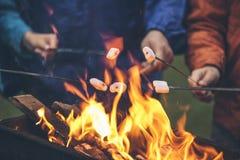 Mains des amis rôtissant des guimauves au-dessus du feu dans un gril image stock