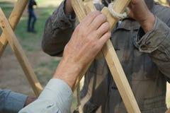 Mains des constructeurs masculins Les hommes établissent le cadre asiatique de yurt Photo libre de droits