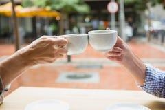 Mains des couples supérieurs grillant des tasses de café Photographie stock libre de droits