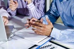 Mains des employés de bureau travaillant sur l'ordinateur portatif Images stock