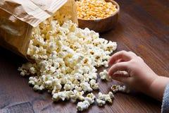 Mains des enfants mangeant du maïs éclaté Images stock