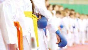Mains des enfants se tenant dans une rangée des karatekas dans les gants banque de vidéos