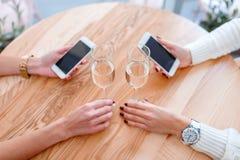 Mains des filles s'asseyant à une table dans un café, tenant les téléphones intelligents et buvant du champagne Photo stock